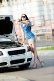 Kvinna som liftar nära den brutna vita bilen Royaltyfri Fotografi