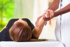 Kvinna som ligger få ner fysisk armbehandling från den physio terapeuten, händer som arbetar på hennes armbågeområde, medicinskt  royaltyfria bilder