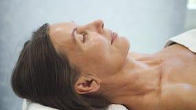 Kvinna som ligger i brunnsortsalong med stängda ögon lager videofilmer