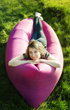 Kvinna som ligger i en uppblåsbar soffa Royaltyfri Foto