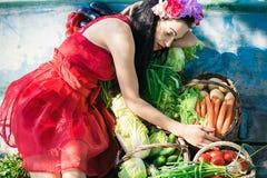 Kvinna som ligger i ett fartyg med grönsaker Royaltyfria Foton