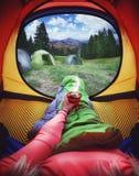 Kvinna som ligger i ett tält med kaffe, sikt av berg och himmel Fotografering för Bildbyråer