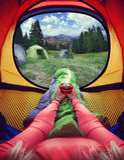 Kvinna som ligger i ett tält med kaffe, sikt av berg och himmel Royaltyfri Foto
