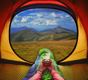 Kvinna som ligger i ett tält med kaffe, sikt av berg och himmel Arkivfoton