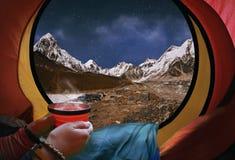 Kvinna som ligger i ett tält med kaffe, sikt av berg och natt s Arkivfoto