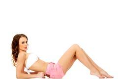 Kvinna som ligger i kortslutningar och behå Royaltyfri Bild