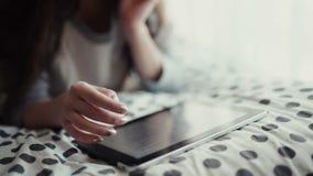 Kvinna som ligger i säng med den digitala minnestavlan som trycker på med fingret ovanför sikt arkivfilmer