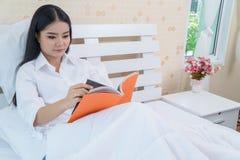 Kvinna som ligger i säng, medan läsa en bok Arkivfoto