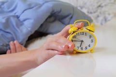 Kvinna som ligger i säng som är roterande av ett ringklockaslut upp Hat som tidigt vaknar upp Selektiv fokus på klockan Royaltyfri Foto