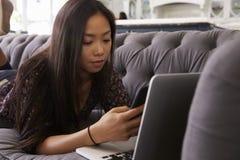 Kvinna som ligger på den Sofa At Home Using Mobile telefonen och bärbara datorn royaltyfri fotografi