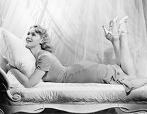 Kvinna som ligger på en chaisevardagsrum med henne ben upp (alla visade personer inte är längre uppehälle, och inget gods finns L Royaltyfri Foto