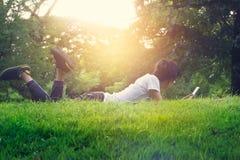 Kvinna som ligger på ett utomhus- gräs Hon kopplar av och genom att använda smartphonen arkivfoto