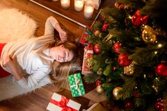 Kvinna som ligger på golvet i jul som hem dekoreras arkivfoton
