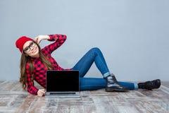 Kvinna som ligger på golvet och visar den tomma bärbar datorskärmen Royaltyfri Fotografi