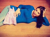 Kvinna som ligger på golvvisning hennes gravida buk royaltyfri foto