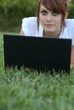 Kvinna som ligger på gräset Fotografering för Bildbyråer