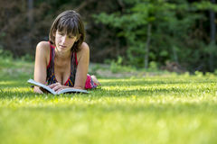 Kvinna som ligger på gräset, medan läsa en bok Arkivbilder