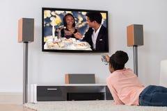 Kvinna som ligger på hållande ögonen på television för matta Royaltyfria Bilder