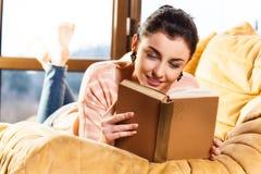 Kvinna som ligger på hennes soffa som hemma läser en bok royaltyfria bilder