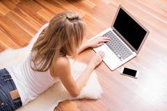 Kvinna som ligger på jordning med bärbara datorn arkivfoto
