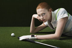 Kvinna som ligger på kurs med golfklubben och bollen royaltyfri foto