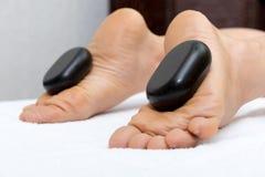 Kvinna som ligger på magen, kvinnlig massös som gör ben och fot massage med varma stenar Arkivbild