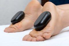 Kvinna som ligger på magen, kvinnlig massös som gör ben och fot massage med varma stenar Arkivfoton