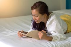 Kvinna som ligger på säng som läser en bok i sovrum royaltyfria bilder