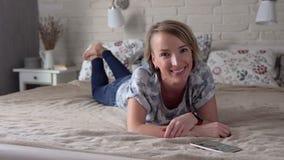 Kvinna som ligger på säng och att le arkivfilmer