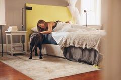 Kvinna som ligger på säng som spelar med hennes älsklings- hund i morgon royaltyfri foto