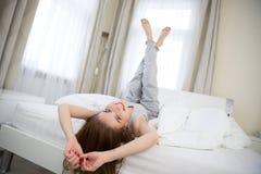 Kvinna som ligger på sängen med lyftta ben upp Arkivfoton