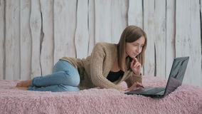Kvinna som ligger på sängen och använder bärbara datorn Arkivbild