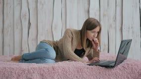 Kvinna som ligger på sängen och använder bärbara datorn Royaltyfri Bild