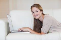 Kvinna som ligger på sofaen som surfar internet Royaltyfria Bilder
