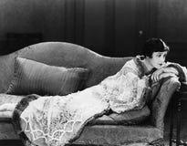 Kvinna som ligger på soffan (alla visade personer inte är längre uppehälle, och inget gods finns Leverantörgarantier att det ska  Royaltyfri Foto