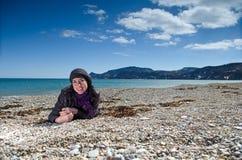 Kvinna som ligger på stranden Fotografering för Bildbyråer
