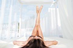 Kvinna som ligger på strandsängen med henne ben upp Arkivfoto