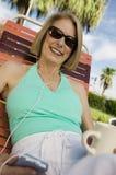 Kvinna som ligger på sunlounger som lyssnar till ståenden för spelare för bärbar musik. Arkivbild