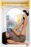 Kvinna som ligger på windowsilen arkivfoton
