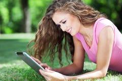 Kvinna som ligger på gräs med den digitala minnestavlan Arkivfoton