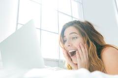 Kvinna som ligger på sängen och använder bärbar datordatoren Arkivfoto