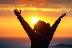 Kvinna som lovordar och tycker om guld- solnedgång Arkivfoto
