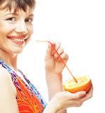 Kvinna som läppjar orange fruktsaft med ett sugrör Arkivfoto