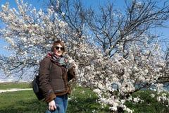 Kvinna som luktar blomman för äppleträd arkivbild
