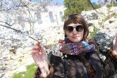 Kvinna som luktar blommor av äppleträdet arkivbilder