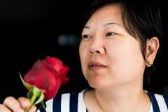 Kvinna som luktar den röda rosblomman i dag för valentin` s Royaltyfria Foton