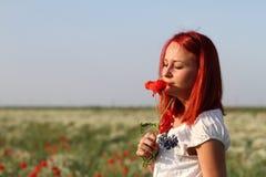 Kvinna som luktar en vallmoblomma Arkivfoton
