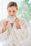 Kvinna som luktar koppen kaffe i vård- Spa Royaltyfri Foto