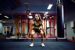 Kvinna som lyfter en viktcrossfit i idrottshallen Skivstång för konditionkvinnadeadlift royaltyfria bilder
