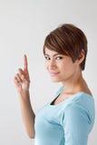 Kvinna som lyfter ett finger eller uppåt pekar hennes finger Royaltyfria Bilder